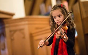 Lily plays violin at a Musicologie concert